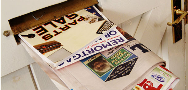 Junk mail pushed through letterbox in door