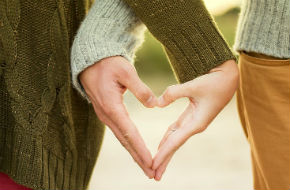 Two people crossing hands to form a heart shape together
