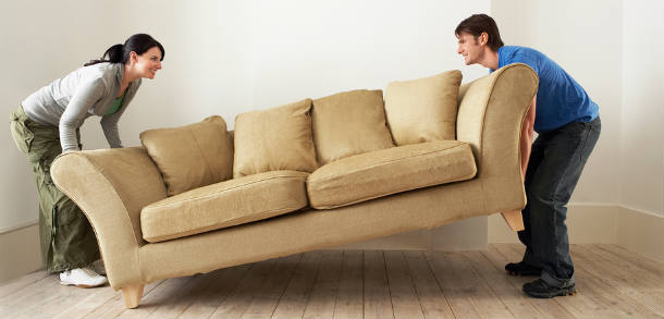 A couple moving a beige sofa