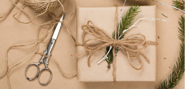 Brown recycable gift wrap, wrapped with twine tied into a bow and a small conifer sprig to decorate