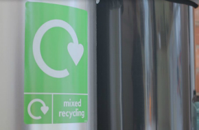 Recycling bin with green poster and recycling swoosh