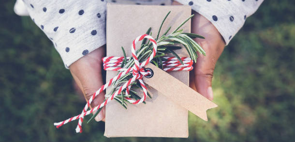Someone holding a rectangle present wrapped in brown paper and decorated with string and foliage