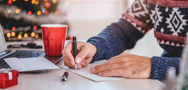 Man wearing a Christmas jumper and writing a Christmas card