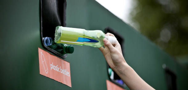 A resident recycling a plastic bottle